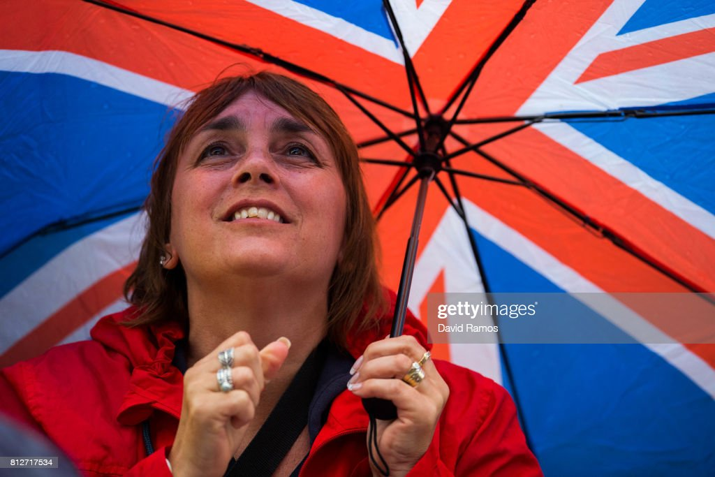 A spectator attempts to keep dry as they watch action on the screen on day eight of the Wimbledon Lawn Tennis Championships at the All England Lawn Tennis and Croquet Club on July 11, 2017 in London, England.