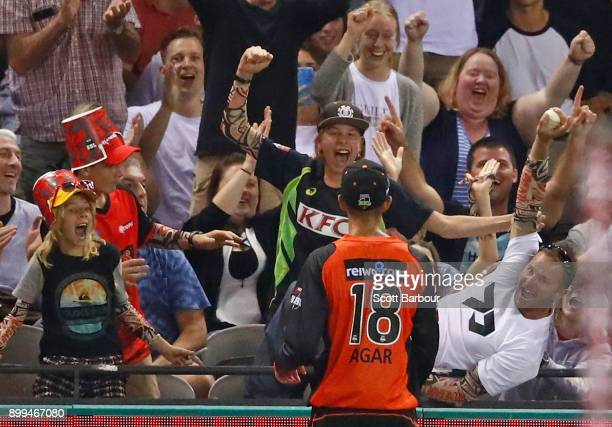 A spectator celebrates after catching a six that was hit into the crowd as Ashton Agar of the Scorchers looks on during the Big Bash League match...