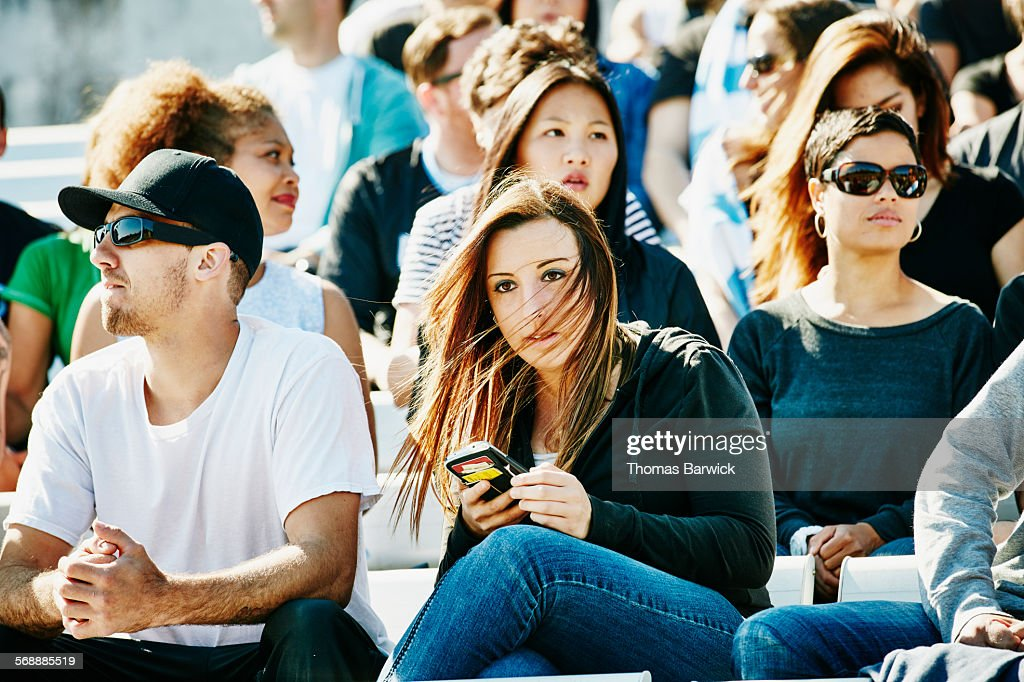 Spectator checking smartphone during sports event : Stock Photo