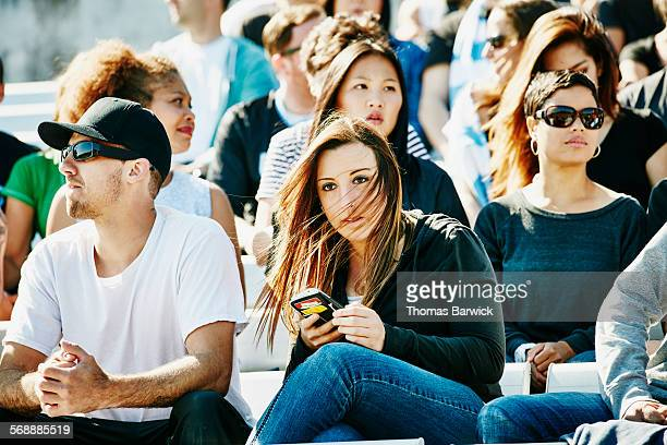 Spectator checking smartphone during sports event
