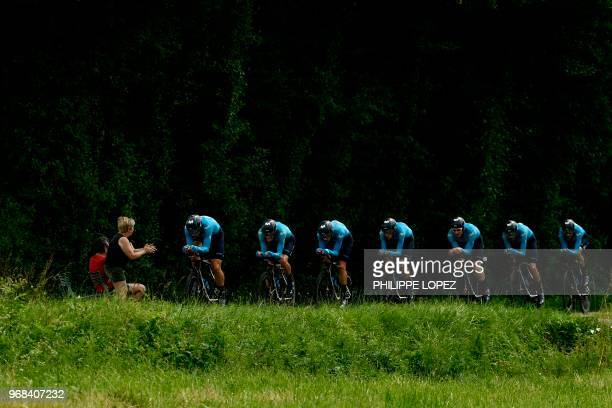 Spectator cheers as riders of Spain's Movistar cycling team compete during the third stage of the 70th edition of the Criterium du Dauphine cycling...