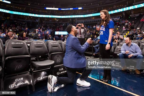 Spectator CJ Williams of Denver proposes to his girlfriend Lauren Lundy also of Denver at the Pepsi Center on December 30 2017 in Denver Colorado...