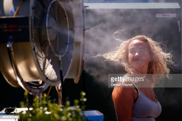 A spectator cools down in front of a mist fan on day four of the 2018 Australian Open at Melbourne Park on January 18 2018 in Melbourne Australia