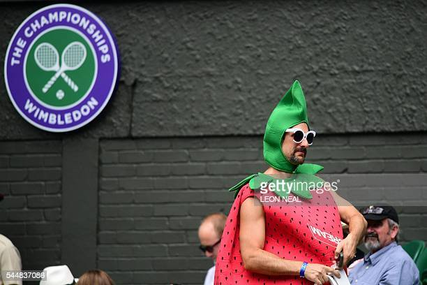 A spectator dressed as a strawberry arrives on centre court on the eighth day of the 2016 Wimbledon Championships at The All England Lawn Tennis Club...