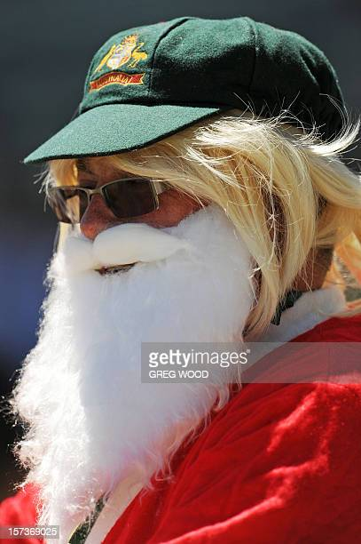 A spectator dressed as Santa Claus and wearing an Australian baggy green cap watches the South African team walk out onto the field at the start of...