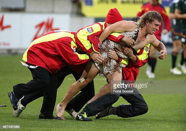 A spectator dressed as Tarzan is ejected from the stadium after getting onto the outer field during the parade of nations at Westpac Stadium on...