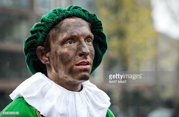 A spectator dressed as 'Zwarte Piet' or 'Black Pete' waits to see Sinterklaas or Sain Nicholas arriving on his barge in Amsterdam on November 16 2014...