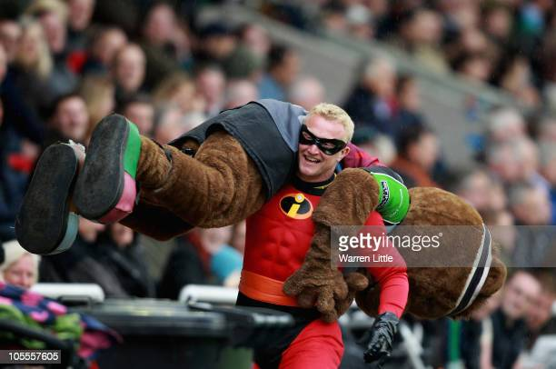 A spectator dressed in a fancy dress carries the Harlequins mascot along the touch line during the Amiln Challenge Cup match between Harlequins and...