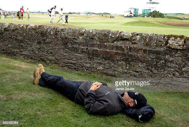 A spectator enjoys an afternoon nap as Bernhard Langer of Germany and Tim Clark of South Africa walk past during the third round of the 134th Open...