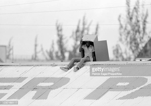 Spectator finds shelter from the sun under a cardboard box while watching the match from the roof of a stand on day five of the 3rd Test match...