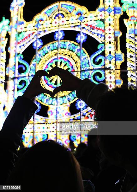 A spectator forms a heart shape with hands at the Kobe Luminarie light festival held to commemorate victims of the 1995 Great Hanshin Earthquake in...