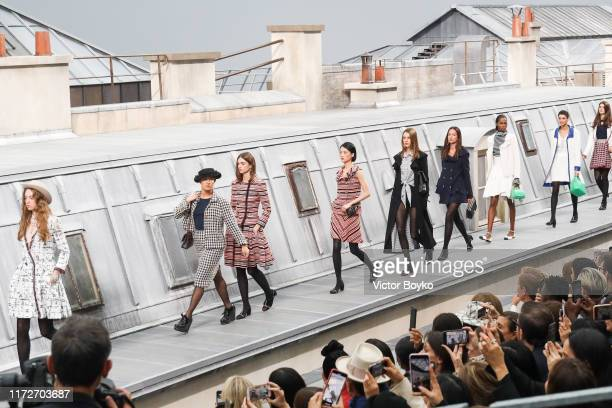 A spectator from the audience climbs the runway to walk with the models during the finale of the Chanel Womenswear Spring/Summer 2020 show as part of...