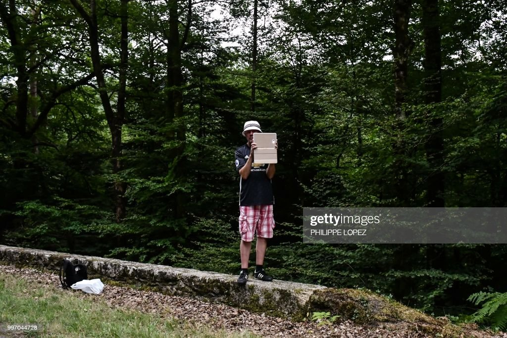 TOPSHOT - A spectator holding a tablet to take photos stands by the side of the route during the sixth stage of the 105th edition of the Tour de France cycling race between Brest and Mur-de-Bretagne Guerledan, western France, on July 12, 2018.