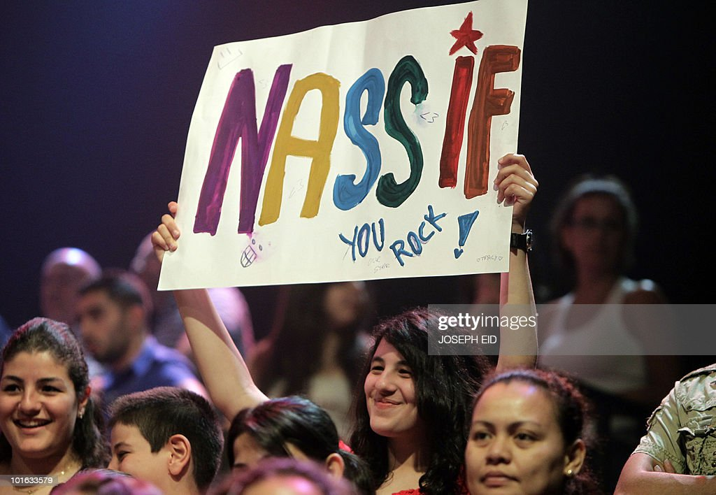 A spectator holds a banner bearing the name of Syrian participant Nassif al-Zeitoun as she attends the final of Star Academy, a highly successful pan-Arab television show, produced by Lebanese Broadcasting Corporation International (LBCI), at its studios in Adma, north of Beirut, late on June 4, 2010.