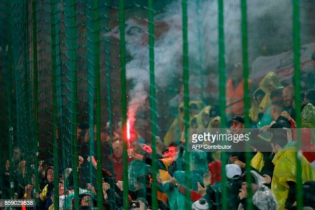 A spectator holds a lit flare in the crowd during the 2018 FIFA World Cup European Qualifying football match between Lithuania and England at the LFF...