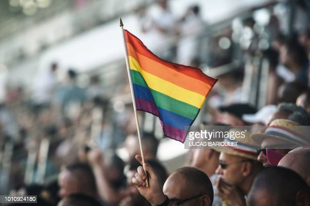A spectator holds a rainbow flag during the opening ceremony of the 2018 Gay Games edition at the Jean Bouin Stadium in Paris on August 4 2018 French...