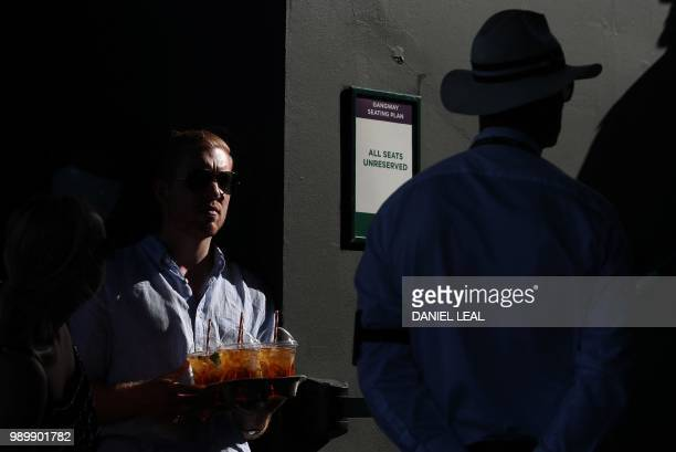 TOPSHOT A spectator holds a tray of Pimms drinks as he waits to takes his seat on a court at The All England Tennis Club in Wimbledon southwest...