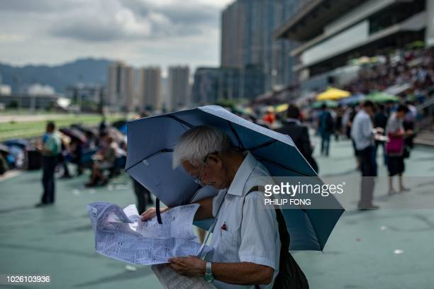A spectator holds an umbrella to shield himself from the sun as he reads horse statistics during the season opening horse race at the Sha Tin...