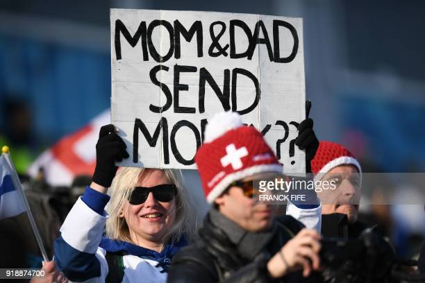 A spectator holds up a placard asking her parents to send money during the men's 15km cross country freestyle at the Alpensia cross country ski...