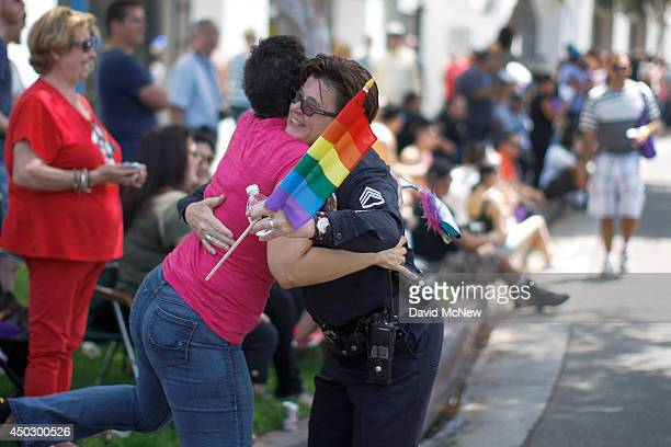 A spectator hugs a Los Angeles police officer marching in the LA Pride Parade on June 8 2014 in West Hollywood California The LA Pride Parade and...
