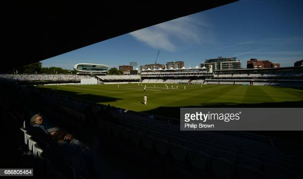 A spectator in a patch of sunshine watches the game during day four of the Specsavers County Championship Division One cricket match between...