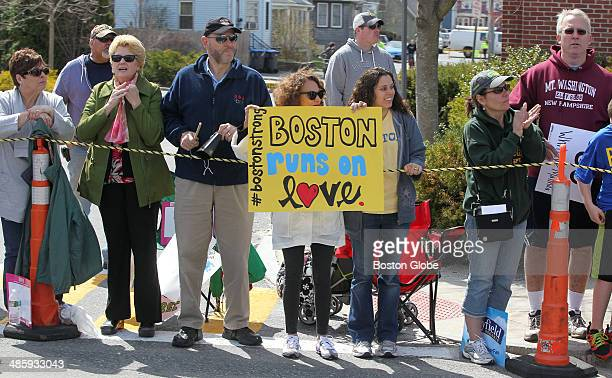 A spectator in Natick holds up a sign that says 'Boston runs on love' and '#bostonstrong' during the 118th Boston Marathon on Monday April 21 2014