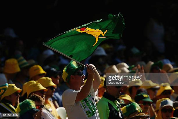 A spectator in the crowd waves a boxing kangaroo flag during day three of the First Ashes Test match between Australia and England at The Gabba on...