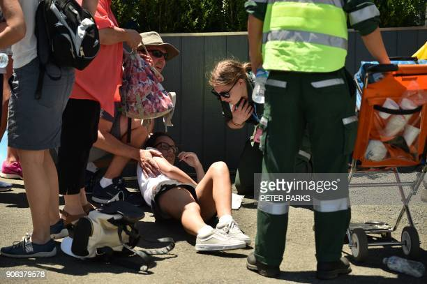 A spectator is assisted by medical personnel after fainting on day four of the Australian Open tennis tournament in Melbourne on January 18 2018 Many...