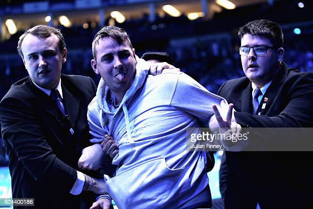 A spectator is removed from the arena by security after attempting to get onto the court during the men's singles semi final between Novak Djokovic...