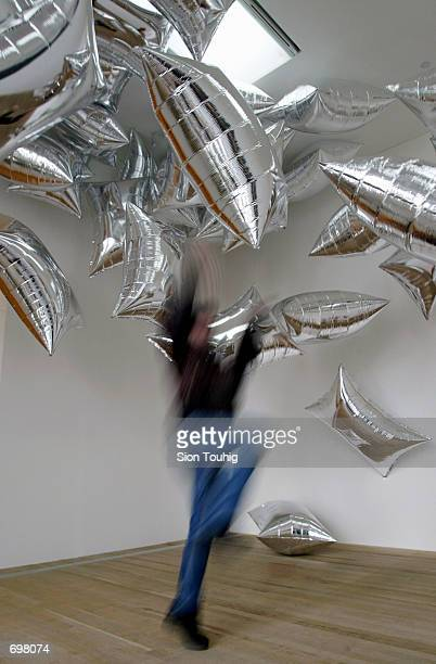 A spectator jumps to catch 'Silver Clouds' a ballon sculpture February 5 2002 at the Andy Warhol retrospective exhibition at the Tate Modern Gallery...
