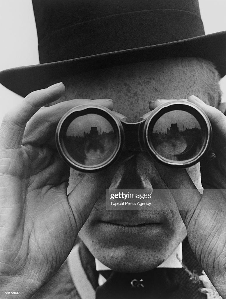 A spectator looking through binoculars at the Derby horse races, Epsom, Surrey, June 1923.
