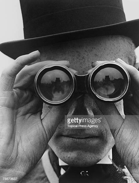 A spectator looking through binoculars at the Derby horse races Epsom Surrey June 1923