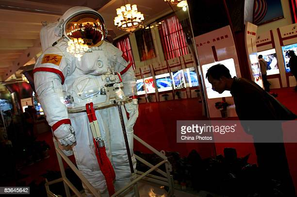 A spectator looks at the Feitian spacesuit during the 'Feitian Documentary Photography Exhibition of Shenzhou VII Manned Space Flight'at the Military...