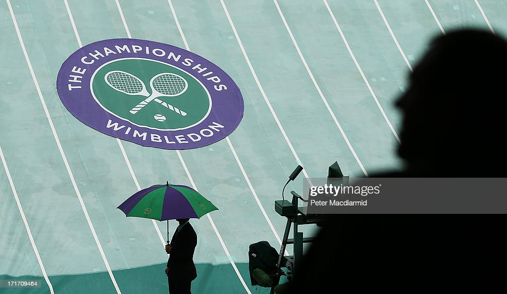 A spectator looks at the rain cover on court one at the Wimbledon Lawn Tennis Championships on June 28, 2013 in London, England. Rain has delayed play on the outside courts today on day five of the tournament.