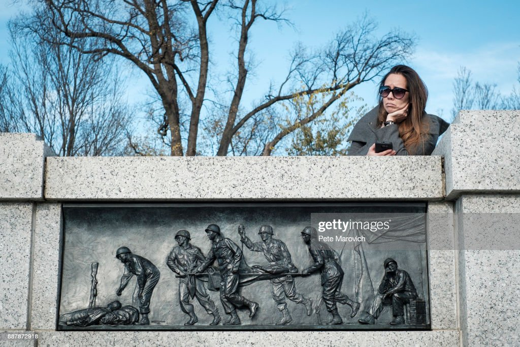 A spectator looks on as the Friends of the National World War II Memorial and the National Park Service, commemorate Pearl Harbor Remembrance Day on December 7, 2017 in Washington, DC. World War II veterans and Pearl Harbor survivors placed wreaths at the Freedom Wall to commemorate the more than 400,000 Americans who lost their lives during World War II, including the more than 2,400 who lost their lives on December 7, 1941.