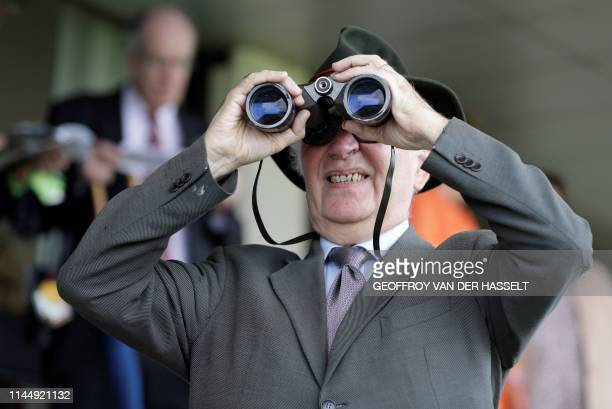 A spectator looks through binoculars during the 141st edition of the Grand SteepleChase de Paris on May 19 at the Auteuil Hippodrome in Paris