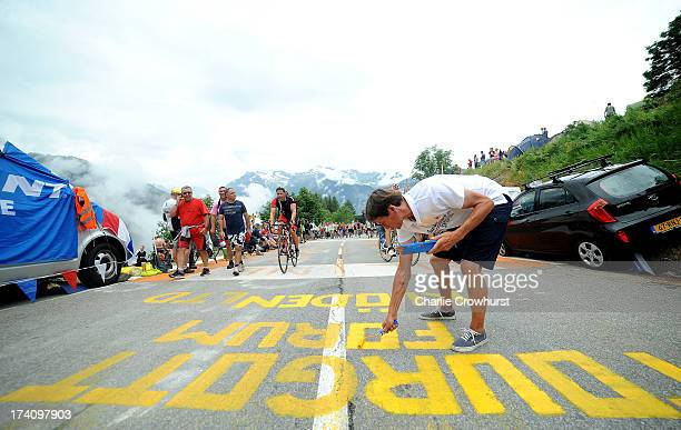 A spectator paints the road during stage eighteen of the 2013 Tour de France a 1725KM road stage from Gap to l'Alpe d'Huez on July 18 2013 in Alpe...