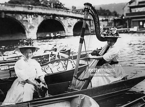 A spectator playing a concert harp in a boat at Henley Royal Regatta Oxfordshire 1908 on the Thames