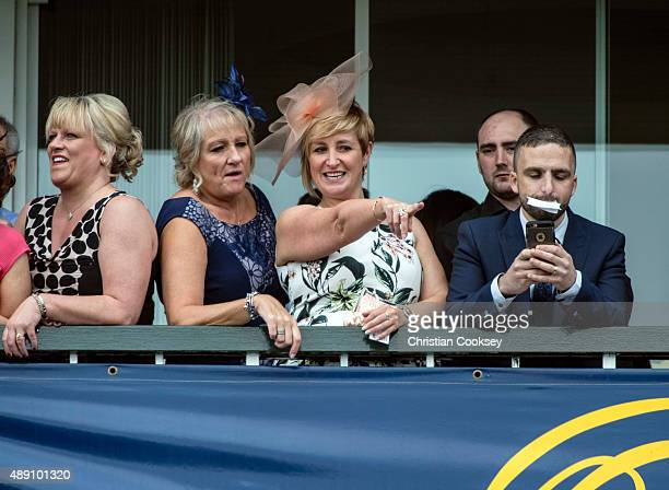 A spectator points to something in the crowd before the third race at Ayr racecourse on September 19 2015 in Ayr Scotland
