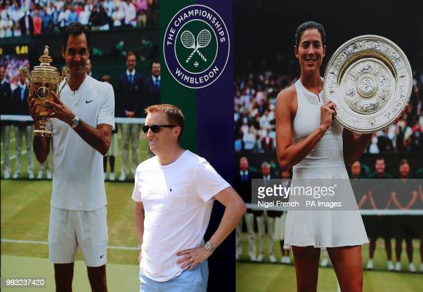 A spectator poses in front of a board featuring last years champions Roger Federer and Garbine Muguruza on day six of the Wimbledon Championships at...