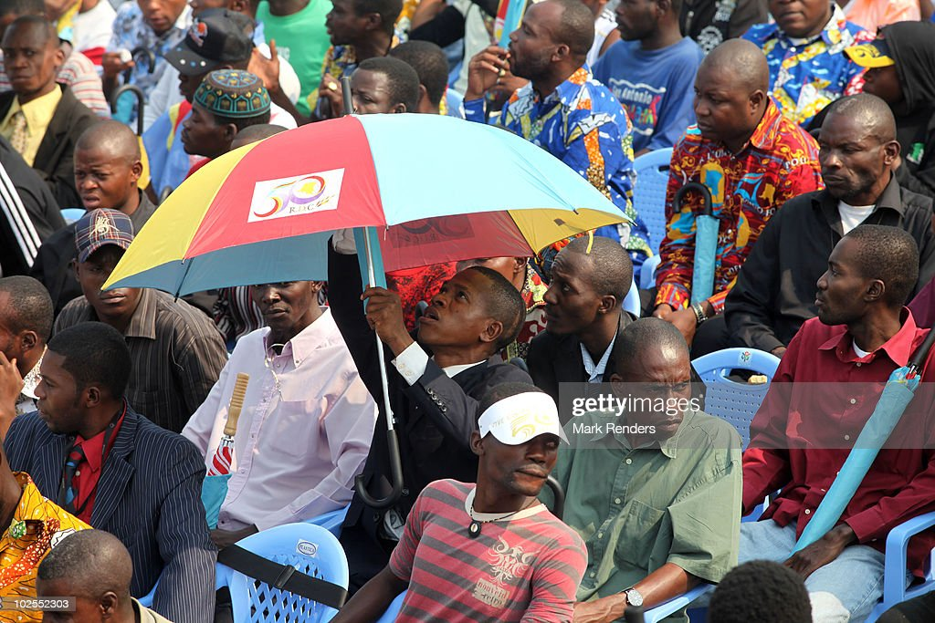 A spectator raises an umbrella as crowds gather to watch the 50th anniversary parade marking the independence of the Democratic Republic of Congo on June 30, 2010 in Kinshasa, Democratic Repuplic of Congo. King Albert II of Belgium and Queen Paola of Belgium are on a 3 day state visit and and as guests of the 50th anniversary celebrations.