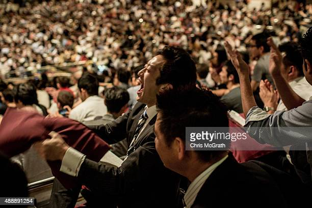 A spectator reacts to the outcome of a fight during the Tokyo Grand Sumo tournament at the Ryogoku Kokugikan on September 17 2015 in Tokyo Japan...