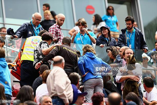 A spectator receives medical attention whiich stopped the third round match between Andy Murray of Great Britain and Gilles Simon of France during...