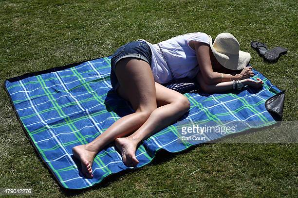 A spectator relaxes in the sun on Murray Mound on day two of Wimbledon tennis tournament on June 30 2015 in London England The 129th tournament to be...