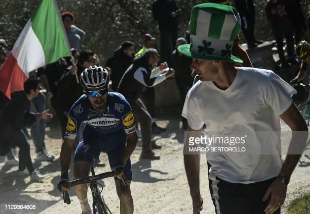 Spectator runs along France's Julian Alaphilippe during the one-day classic cycling race Strade Bianche on March 9, 2019 in Siena, Tuscany.