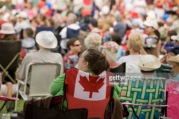 A spectator seated in Canadian maple leaf flag chair waits for the Canada Day festivities to begin in this 2008 Penticton British Columbia Canada...