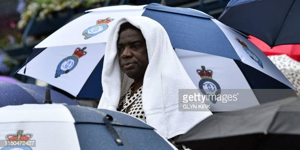 A spectator shelters from the rain with a towel as rain delays play ahead of the men's singles firstround match at the ATP Queen's Club Championships...