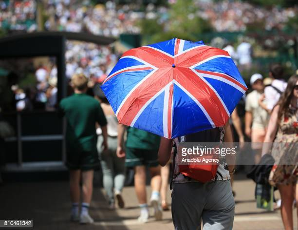 A spectator shelters from the sunshine under a Union Jack umbrella on day five of the 2017 Wimbledon Championships at the All England Lawn and...