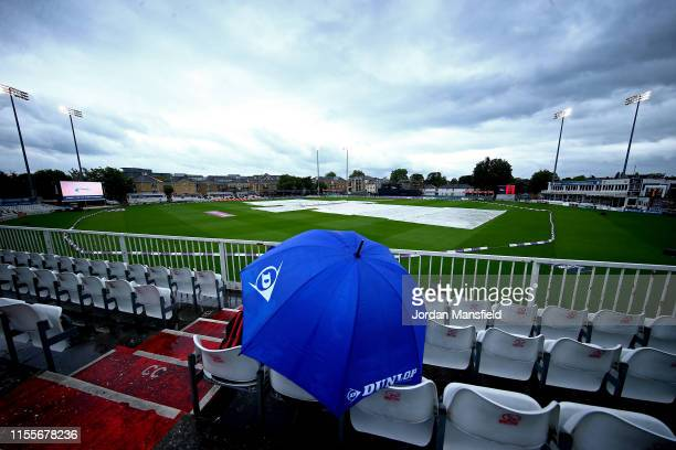 Spectator shelters under an umbrella as rain delays play during the 3rd One Day International match between England Women and West Indies Women at...
