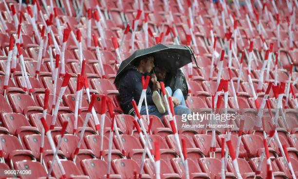 Spectator shelters under an umbrella as rain falls before the International Friendly match between Austria and Germany at Woerthersee Stadion on June...